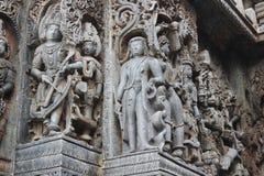 Den Hoysaleswara tempelväggen sned med en skulptur som ser som utlänning Royaltyfria Foton