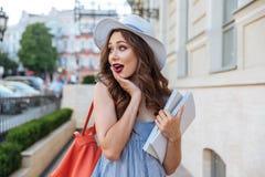Den häpna kvinnan med ryggsäcken och mellanrumet bokar att gå på gatan Fotografering för Bildbyråer
