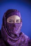 Den härliga arabiska kvinnan med traditionellt skyler på hennes framsida, intens Royaltyfri Bild