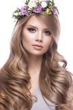 Den härliga blonda flickan med ett försiktigt smink, krullar och blommar i hennes hår Arkivbilder