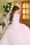 Den härliga bruden i elegant vit bröllopsklänning och skyler med långt lockigt hår som inomhus poserar Royaltyfri Fotografi