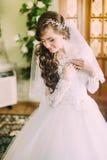 Den härliga bruden i elegant vit bröllopsklänning och skyler med långt lockigt hår som inomhus poserar Royaltyfria Bilder