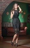 Den härliga brunettdamen i elegant svart snör åt klänningen som poserar i en tappningplats Arkivbild