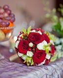 Den härliga buketten av steg blommor på tabellen. Bröllopbukett av röda rosor. Elegant bröllopbukett på tabellen på restaurangen Royaltyfria Bilder