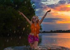 Den härliga flickan i ljus kläder i sjön lyfter springbrunnen av färgstänk av vatten på solnedgången Arkivfoton