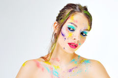 Den härliga flickan med färgrik målarfärg plaskar på framsida Arkivbild