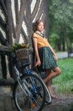 Den härliga flickan som bär en trevlig klänning med högskolablicken som har gyckel parkerar in, med cykeln som bär en härlig korg Arkivfoton