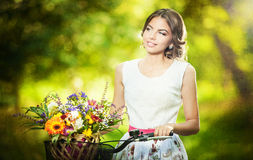 Den härliga flickan som bär en trevlig vit klänning som har gyckel parkerar in, med cykeln som mycket bär en härlig korg av blommo Arkivbilder