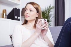 Den härliga flickan vilar på soffan med kaffe Arkivbild