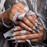 Den härliga handen av flickan med det mörka hudkneget av akryl spikar med spikar ovanligt fotmoy Arkivbilder