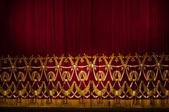 Den härliga inomhus teateretappen hänger upp gardiner med dramatisk belysning Arkivfoto