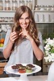 Den härliga kvinnan bantar på äta sötsaker i hemlighet Royaltyfri Bild