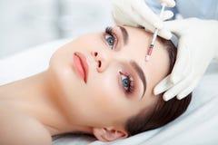 Den härliga kvinnan får injektionen i hennes framsida. Kosmetisk kirurgi Royaltyfri Bild