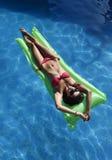 Den härliga kvinnan, i att ligga för bikini, kopplar av på flöteluftmadrass på simbassängen för semesterhotellsemesterorten Arkivfoton