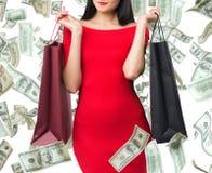 Den härliga kvinnan i en röd klänning rymmer utsmyckade shoppingpåsar Falla ner dollaranmärkningar isolerat Fotografering för Bildbyråer