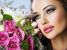Den härliga kvinnan med buketten av ny spting blommar på framsidan Arkivbild