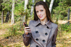 Den härliga kvinnan med en mobiltelefon går på i trä Arkivfoto