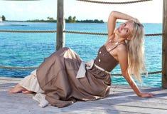 Den härliga kvinnan på en träställning .portrait mot det tropiska havet Arkivbilder