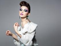 Den härliga kvinnan som bär blått smink, och vit pälsfodrar att posera i studion Arkivfoton