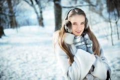 Den härliga kvinnan som går i earmuff, stack tumvanten och pälslaget har gyckel i vinterskog Arkivbild