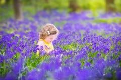 Den härliga litet barnflickan i blåklocka blommar i vårskog Royaltyfri Fotografi