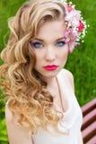 Den härliga mjuka söta flickan i en vit klänning med en bröllopfrisyr krullar ljus makeup och röda kanter med blommor i hennes hå Arkivbild