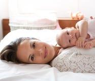 Den härliga modern vilar i säng med behandla som ett barn dottern Arkivbilder
