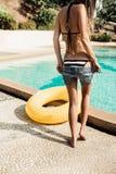 Den härliga slanka flickan i sexig randig bikini tar av hennes kortslutningar Royaltyfria Bilder