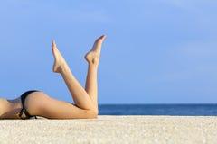Den härliga släta modellen lägger benen på ryggen att vila på sanden av stranden Royaltyfri Fotografi