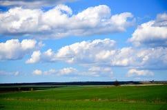 Den härliga soliga dagen i berglandskap med skurkroll fördunklar i den blåa himlen Arkivbild