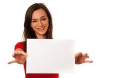 Den härliga unga affärskvinnan som visar ett tomt kort, isolerade ove Arkivfoto