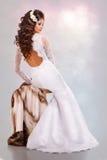 Den härliga unga brunettkvinnan i en bröllopsklänning sitter på en minkpäls tillbaka Royaltyfri Fotografi