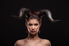 Den härliga unga flickan med horn gillar jäkel eller ängel Arkivfoton