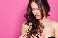 Kvinnan borstar hår Arkivbild