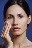 Den härliga unga kvinnan med vård- flår tar bort makeup från vända mot Arkivfoto