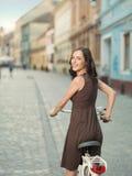 Den härliga unga kvinnan på cykeln vänder huvudet Royaltyfri Foto