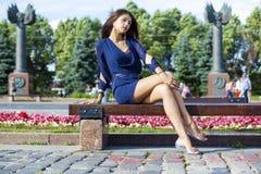 Den härliga unga kvinnan sitter på en bänk Arkivfoto