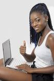 Den härliga unga kvinnan som använder en bärbar datorvisning, tummar upp Fotografering för Bildbyråer