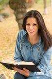 Den härliga unga kvinnan som läser en bok parkerar in, på nedgången Arkivfoton