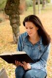Den härliga unga kvinnan som läser en bok parkerar in, på nedgången Royaltyfria Foton