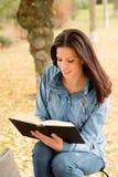 Den härliga unga kvinnan som läser en bok parkerar in, på nedgången Arkivfoto