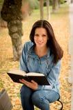 Den härliga unga kvinnan som läser en bok parkerar in, på nedgången Arkivbild