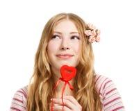 Den härliga unga le kvinnan i fundersamt poserar med rött valent Royaltyfri Bild