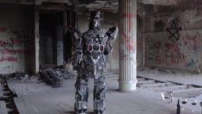 Den Humanoid roboten står med hans baksida i hatt i övergiven byggnad footage Android på datum med exponeringsglas och flaskan av stock video