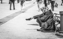 Den hungriga hemlösa tiggarekvinnan tigger för pengar på den stads- gatan i staden från folk som förbi går, social dokumentär beg arkivbild