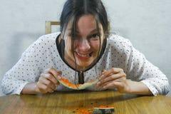 Den hungriga kvinnan äter snabbt en vattenmelon Äta som ett svin royaltyfri fotografi