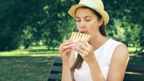 Den hungriga kvinnan som äter smörgåsen parkerar in Turisten som har lunch parkerar offentligt, att tycka om solig dag för sommar lager videofilmer