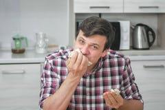 Den hungriga mannen äter shawarma på köket hemma, snabbt för att äta denna arkivfoton