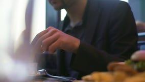 Den hungriga mannen som äter fransman, steker att doppa den in i sås, snabbt mellanmål i kafé stock video