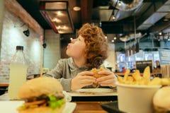 Den hungriga pojken äter hamburgaren i restaurang Royaltyfri Foto